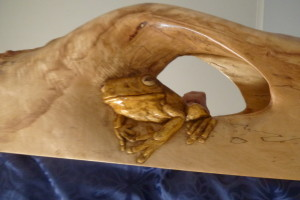 Frog coming through carved frame